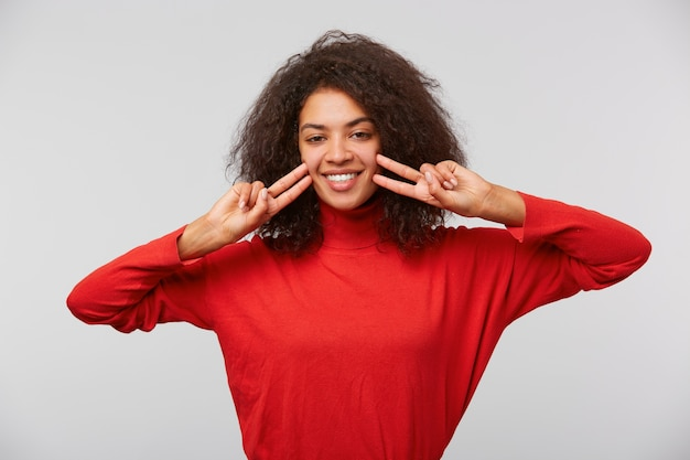 Gros plan d'une jeune femme heureuse montrant le geste de paix