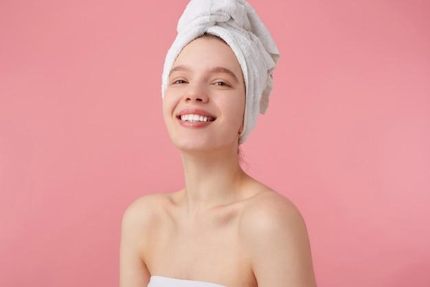 Gros plan d'une jeune femme joyeuse après spa avec une serviette sur la tête, sourit largement, a l'air heureux et apprécié, se dresse.