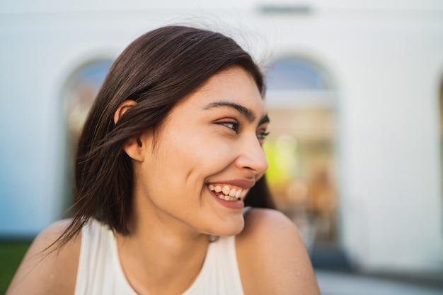 Gros plan d'une jeune femme latine souriante.