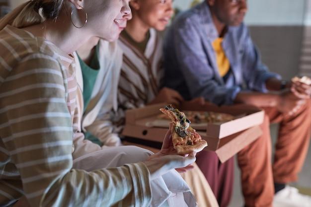 Gros plan sur une jeune femme mangeant de la pizza en regardant la télévision avec des amis à la maison éclairée par la lumière bleue, espace pour copie