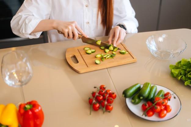Gros plan d'une jeune femme méconnaissable coupant du concombre frais cuisinant une salade de nourriture assise