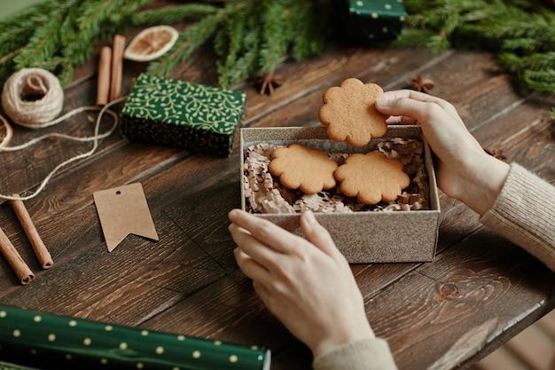 Gros plan d'une jeune femme méconnaissable emballant des biscuits faits maison dans un emballage cadeau de noël au bois rustique...