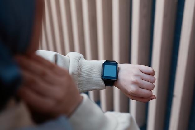 Gros plan sur une jeune femme moderne vérifiant la montre intelligente pendant la course du matin, espace de copie