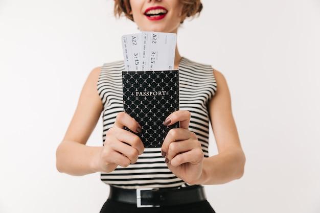 Gros plan d'une jeune femme montrant un passeport avec des billets
