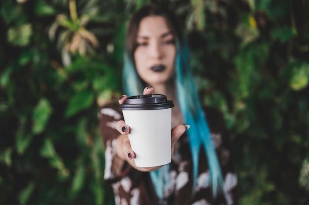 Gros plan d'une jeune femme montrant une tasse de café à emporter