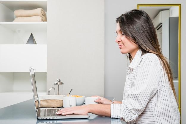 Gros plan, jeune, femme, petit déjeuner, table, utilisation, ordinateur portable