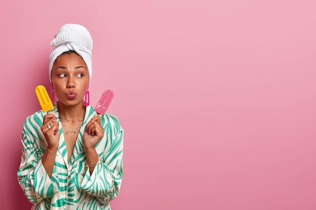 Gros plan sur la jeune femme portant une robe et une serviette enveloppée sur la tête