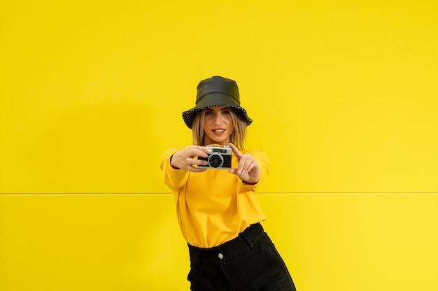 Gros plan d'une jeune femme de race blanche en jaune avec un appareil photo posant pour une photo
