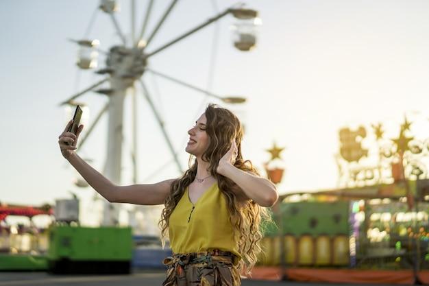 Gros plan d'une jeune femme de race blanche prenant selfie sur téléphone mobile dans un parc