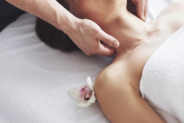 Gros plan d'une jeune femme reçoit un massage au salon de beauté. procédures pour la peau et le corps.