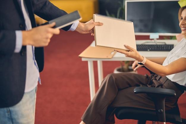 Gros plan d'une jeune femme remettant un carnet de croquis en spirale à un collègue et souriant alors qu'il était assis dans une chaise de bureau