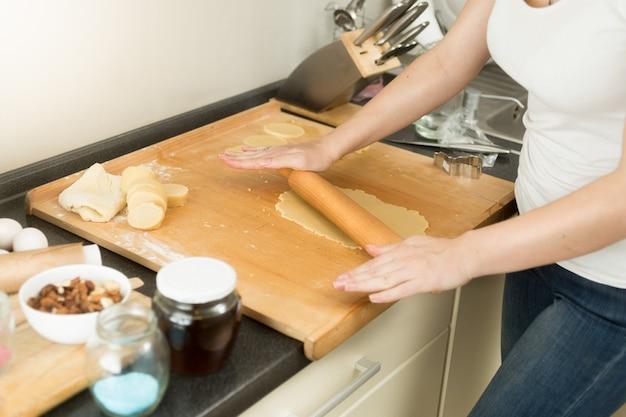 Gros plan de la jeune femme rouler la pâte sur planche de bois avec goupille