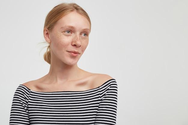 Gros plan sur jeune femme rousse attrayante avec une coiffure décontractée isolée