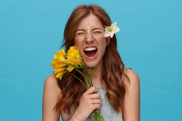 Gros plan d'une jeune femme rousse attrayante gardant les yeux fermés tout en grimaçant son visage, ayant une fleur blanche dans ses cheveux en se tenant debout sur fond bleu