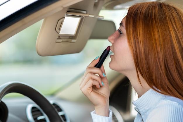 Gros plan d'une jeune femme rousse chauffeur corrigeant son maquillage avec du rouge à lèvres rouge foncé