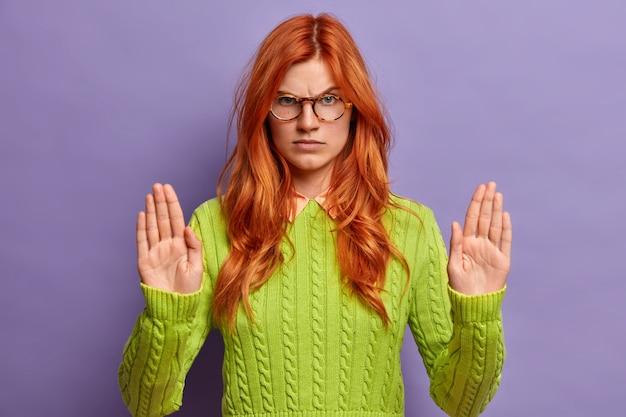 Gros plan sur une jeune femme rousse faisant des gestes
