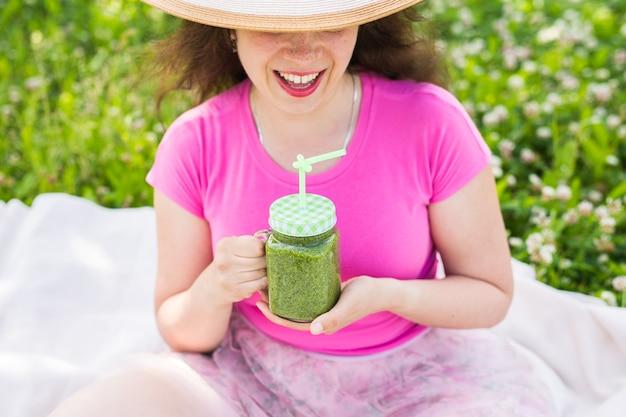Gros plan sur une jeune femme s'amuser dans le parc et boire des smoothies verts lors d'un pique-nique.