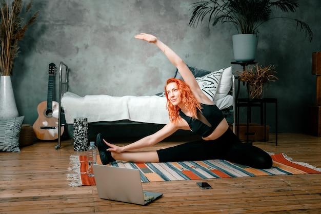 Gros plan d'une jeune femme se repose, faire de l'exercice le matin, étirer les jambes sur le sol à la maison