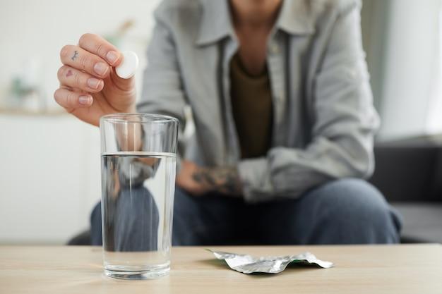Gros plan, de, jeune femme, séance canapé, devant, table, et, jetant la pilule, dans, les, verre eau