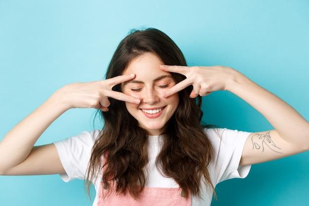 Gros plan sur une jeune femme séduisante avec une peau du visage propre et éclatante, regardant vers le bas et souriant heureux sho ...