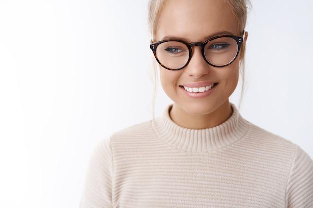 Gros plan d'une jeune femme séduisante, tendre et timide, de 25 ans, en pull et lunettes en détournant les yeux rougissant idiot et mignon souriant faisant largement la promotion de lunettes à la mode sur fond blanc