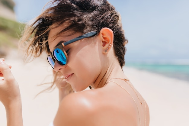 Gros plan d'une jeune femme sensuelle aux cheveux noirs en lunettes de soleil scintillantes. belle femme détendue debout sur la plage de sable en matinée chaude.