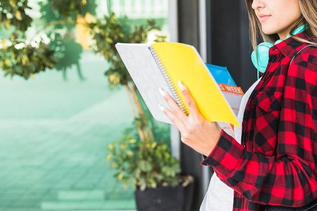 Gros plan d'une jeune femme souriante, lisant des livres à l'extérieur