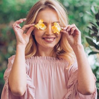 Gros plan d'une jeune femme souriante qui couvre ses yeux avec du freesia jaune