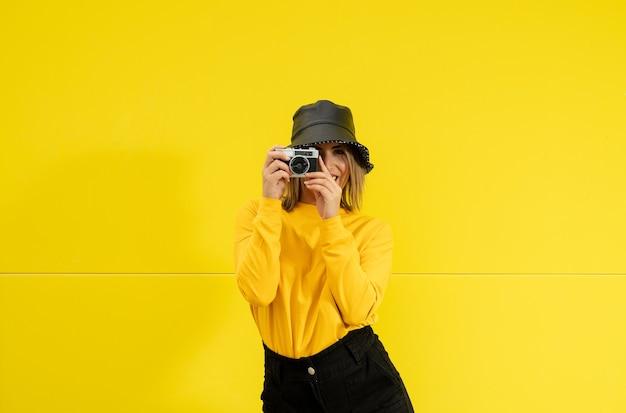 Gros plan d'une jeune femme souriante de race blanche en jaune prenant une photo
