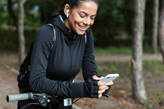 Gros plan d'une jeune femme souriante de remise en forme à cheval sur un vélo dans le parc, écouter de la musique avec des écouteurs, tenant un téléphone mobile