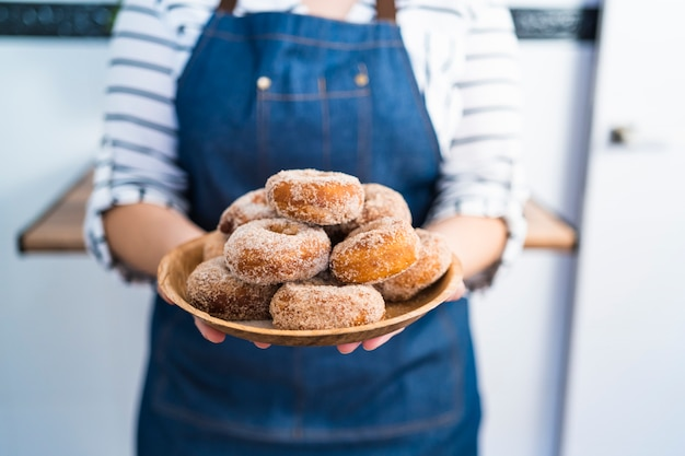Gros plan d'une jeune femme en tablier en jean tenant une assiette de beignets faits maison fraîchement cuits