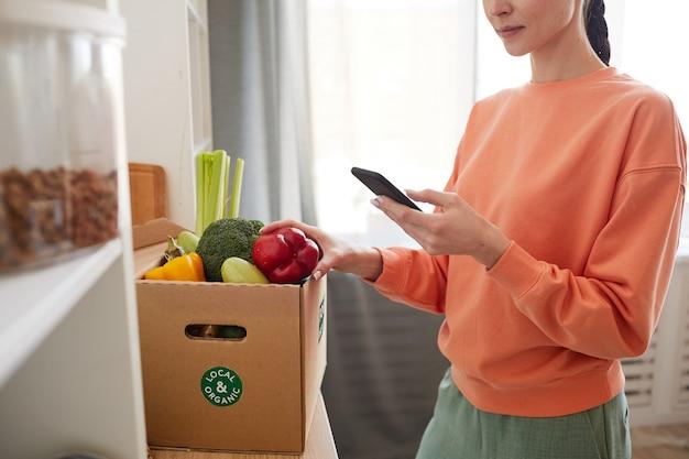 Gros plan d'une jeune femme en tapant un message sur son téléphone mobile en se tenant debout près de la boîte en carton avec des légumes frais