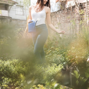 Gros plan, de, jeune femme, tenant, arrosoir, debout, entre, les, plantes en pot