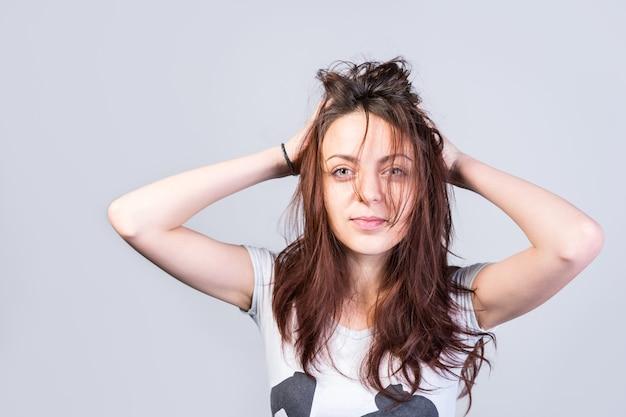 Gros plan jeune femme tenant ses longs cheveux en désordre tout en regardant la caméra sérieusement sur un fond gris.