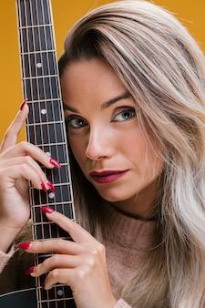 Gros plan, de, jeune femme, tenue, guitare