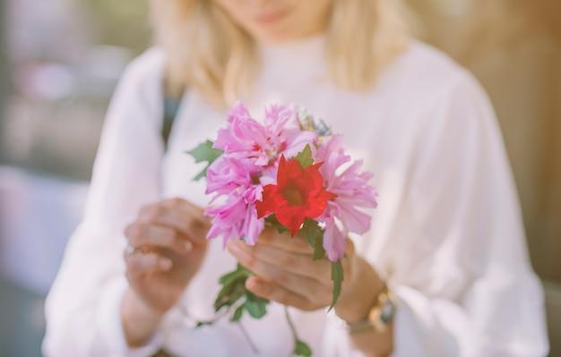 Gros plan, de, jeune femme, tenue, pourpre et rouge, fleur, dans, mains
