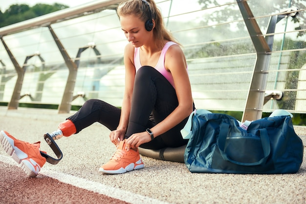 Gros plan sur une jeune femme en vêtements de sport et un casque avec une prothèse de jambe la liant
