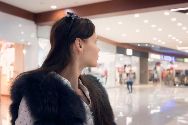 Gros plan d'une jeune fille brune dans un centre commercial en regardant loin de la caméra. une belle femme se tient dans la zone de marche du centre commercial et regarde au loin. la fille cherche quelque chose dans le centre commercial.