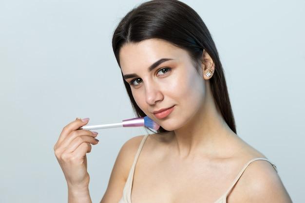 Gros plan d'une jeune fille en haut clair sur fond blanc faisant un maquillage du visage. une jolie femme tient un pinceau cosmétique près de son visage et sourit.