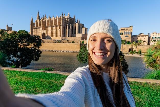 Gros plan d'une jeune fille prenant un selfie avec la cathédrale de palma, une femme à la peau claire porte un pull et un chapeau de laine blanche