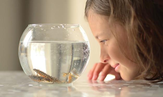 Gros plan d'une jeune fille regardant ses poissons sous l'eau