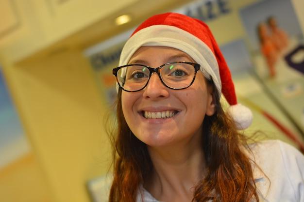 Gros plan d'une jeune fille souriante avec une casquette de noël