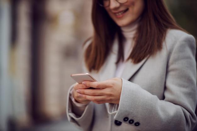 Gros plan d'une jeune fille souriante dans un manteau debout dans la rue et à l'aide d'un téléphone intelligent pour envoyer des sms.