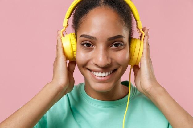 Gros plan de jeune fille souriante de femme afro-américaine en sweat-shirt vert posant isolé sur un mur rose pastel. concept de mode de vie des gens. écoutez de la musique avec des écouteurs.