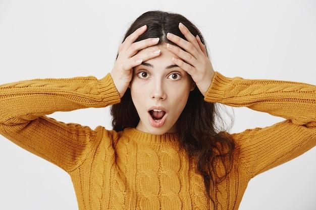 Gros plan d'une jeune fille surprise et étonnée, bouche ouverte fascinée, regardant l'offre de vente ou de remise