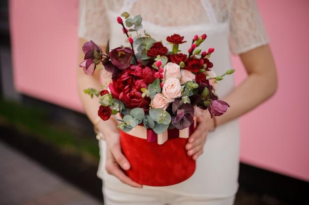 Gros plan d'une jeune fille tenant un bouquet dans une boîte à chapeau