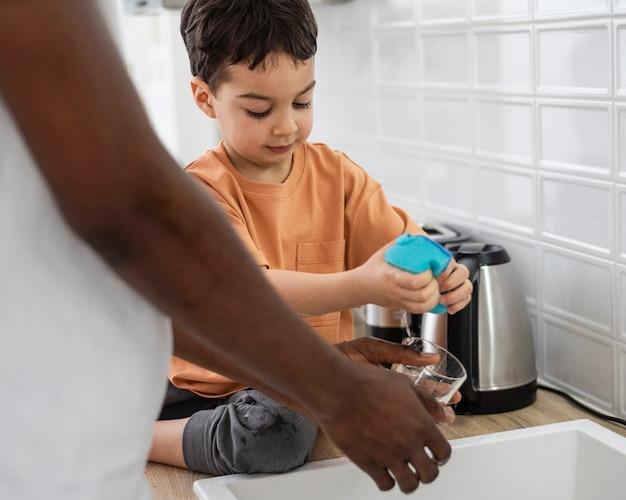 Gros plan sur le jeune garçon aidant avec la vaisselle