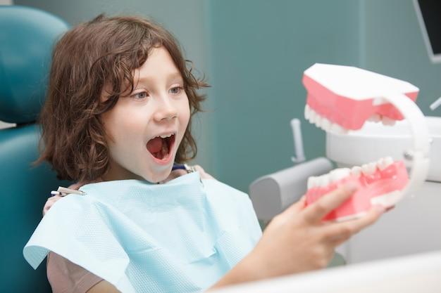 Gros plan d'un jeune garçon heureux jouant avec un modèle de grande mâchoire à la clinique dentaire