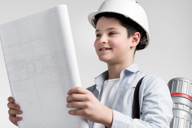 Gros plan, jeune garçon, lecture, plan construction