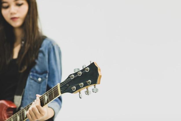 Gros plan d'une jeune guitariste jouant de la guitare électrique. mise au point sélective sur la guitare électrique avec un joueur flou isolé sur fond blanc. concept de mode de vie des adolescents
